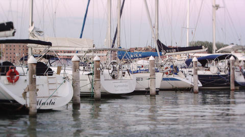 Static shot of the stern of some sailboats docked in the marina bobbing on genti Footage