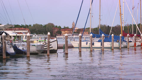 Panning shot of the stern of some sailboats docked in the marina. Public Gardens Footage