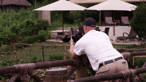 White man takes photos over wooden fence Footage