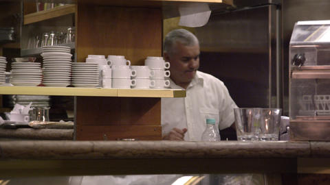 Static shot of a man working in the back of an Italian cafe Footage