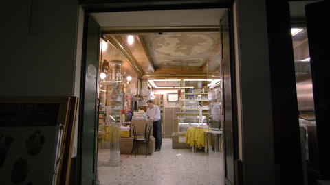 Tilting down shot from outside looking in on an Italian cafe Footage