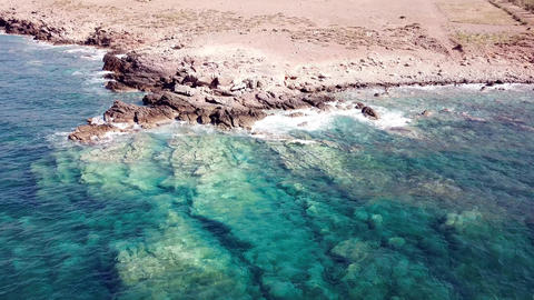 Aerial view of crystal clear waves at a rocky coast with…, Live Action