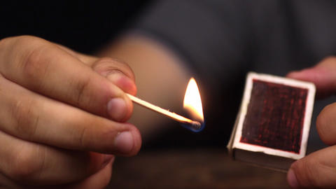 Close-up, a man takes a match out of the box and lights a match Live Action
