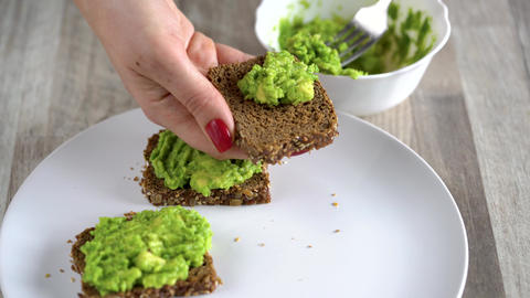 Spreading mashed avocado on toast. Healthy vegan breakfast Live Action