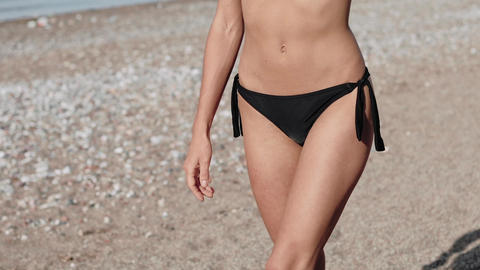 Woman with perfect fit body walking confident on beach. Unrecognizable sexy young woman Footage