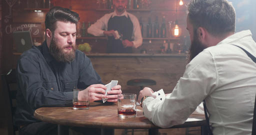 Bearded man having a sip of whiskey while playing cards with a friend Footage