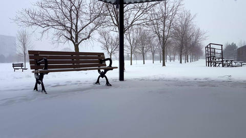 Snowing Scene With Park Bench in Day. Snowy Landscape With Public Park Architecture Under Overcast Footage