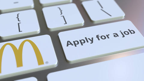 MCDONALD'S company logo and Apply for a job text on the keys of the computer Footage