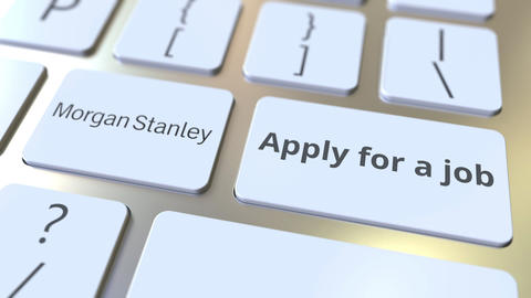 MORGAN STANLEY company logo and Apply for a job text on the keys of the computer Live Action