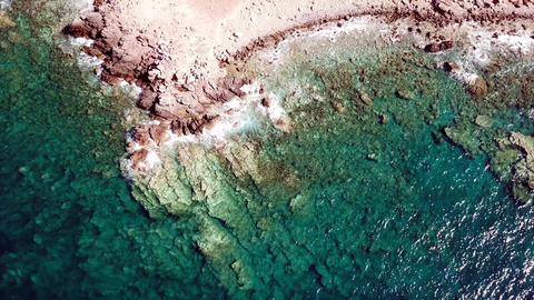 Aerial view of crystal clear waves at a rocky coast with clear blue water - Live Action