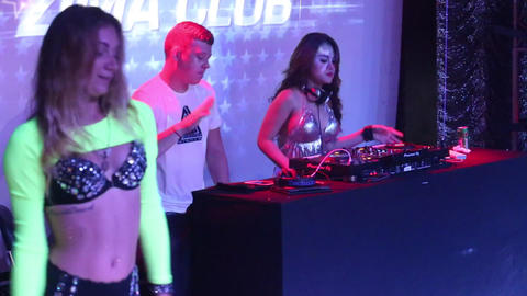popular dj and go-go girls entertain public in club Live Action