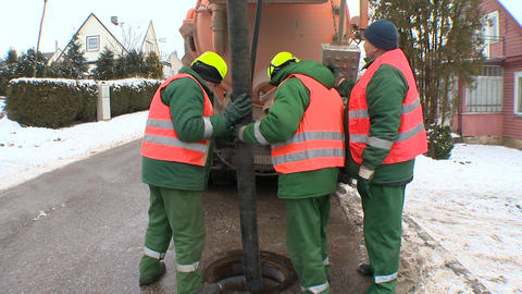 Three operator using long hose to clean sewage hole well from fecal Live Action