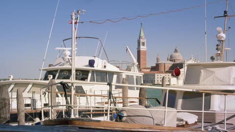 Static shot of a boat docked at a marina with the Island of San Giorgio in the b Footage