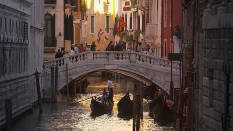 Slow motion shot of people crossing a bridge over a canal in Venice, Italy Footage