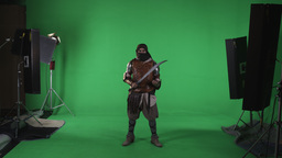 Shot of masked man in arabic armor making intimidating motion with sword. Agains Footage