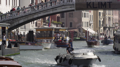 Slow motion shot of the busy Grand Canal with tourists crossing the Ponte Scalzi Footage