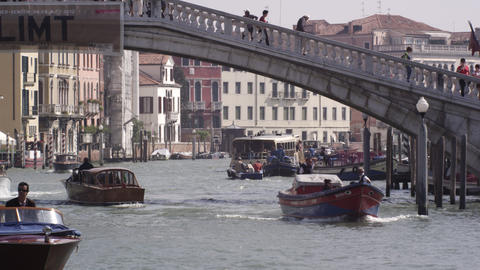 Slow motion shot of motor boats traversing the Grand Canal under the Ponte Scalz Footage