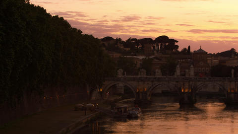 Left-to-right pan of Ponte Sant'Angelo and dome of St. Peter's Basilica at sunse Footage