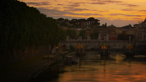 Left-to-right pan of Ponte Sant'Angelo and dome of St. Peter's Basilica at dusk Footage