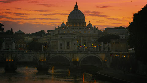 Slight tilt up and pan of Ponte Sant'Angelo and St. Peter's Basilica at dusk Footage