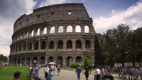 Pedestrians walking by gardens in front of The Colosseum in Rome Italy Footage