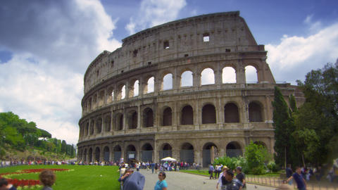 Pedestrians by gardens in front of The Colosseum in Rome Italy Footage