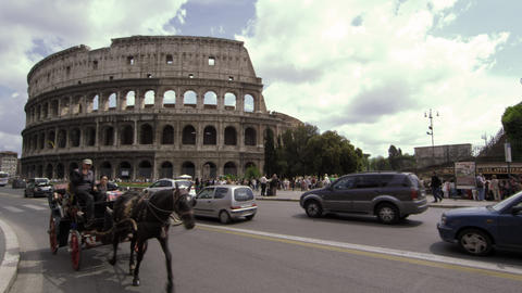 Horse carriage and automobile traffic in from of the Colosseum in Rome Italy Footage