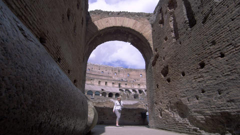 Slow motion footage of tourists walking by an arch in the stands of the Colosseu Footage