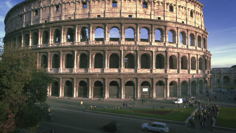 Slow motion, angled pan shot of Colosseum to street Footage