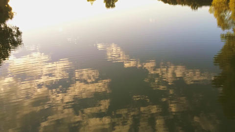 Panning and tilting shot by drone sunset lake reflection smooth water surface Live Action