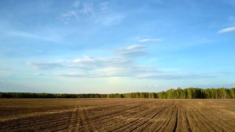 motion above field with plowed brown soil under blue sky Footage