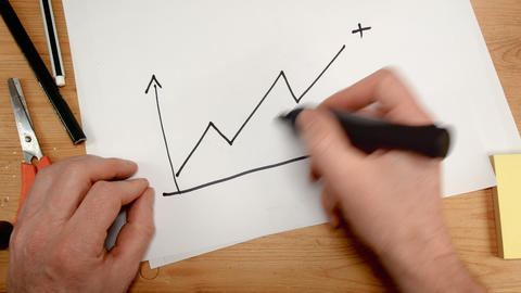 top view, a businessman's hand draws a graph that goes into positive value Archivo