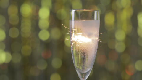 a glass of champagne against a gold bokeh background and sparklers Live Action