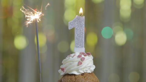 Number 1 birthday celebration candle against a bright lights and golden bokeh background Footage