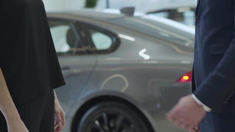 Unrecognized confident professional salesman in a business suit gives a car keys Footage