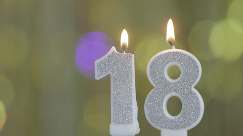 Number 18 birthday celebration candle against a bright lights and golden bokeh background Live Action