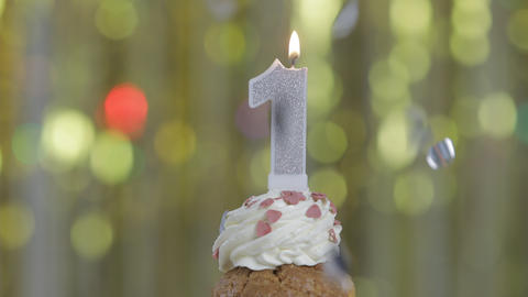 Number 1 birthday celebration candle against a bright lights and golden bokeh background Live Action