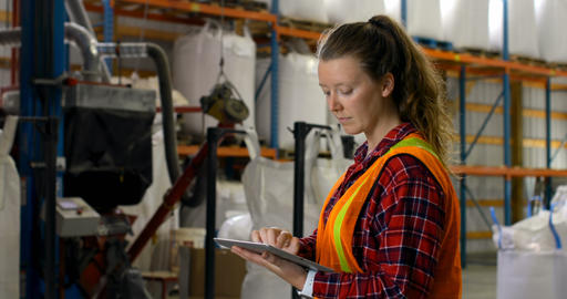 Side view of caucasian female worker working on digital tablet in warehouse 4k Live Action