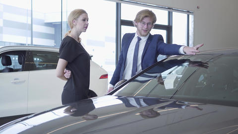 Smiling bearded salesman in business suit showing new auto to successful Live Action