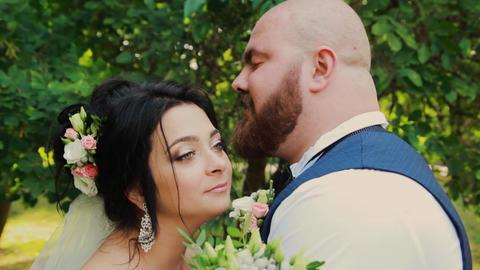 Happy newlyweds walking, hugging, kissing in the park Footage