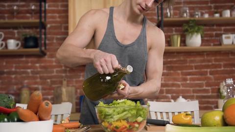 Handsome muscle sportsman is preparing vegan fresh salad pours olive oil in Footage