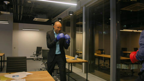 Two Competitive businessmen fighting with boxing gloves in corporate office Footage