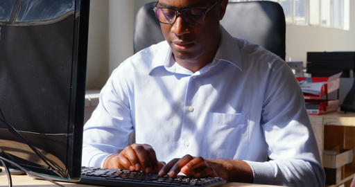 Front view of young black businessman working on desktop pc in a modern office 4k Live Action