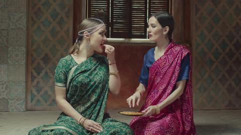 Female friends in sari tasting fragant indian dish Footage