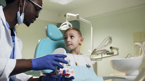 African male dentist showing plastic model of teeth to the little male patient Live Action