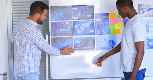Side view of young mixed race male executives discussing over graph in modern office 4k Live Action