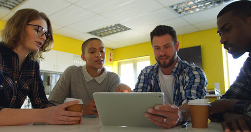 Young mixed race business team discussing over digital tablet in modern office 4k Live Action