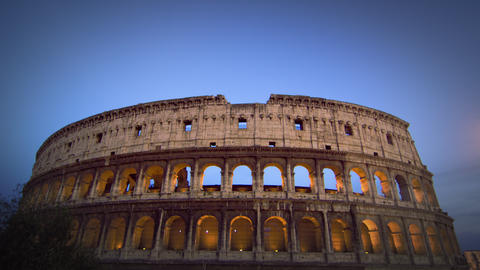 Tilt down from sky to illuminated Colosseum at night Footage