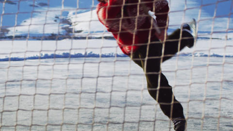 Young boy playing hockey; shoots, slides onto the ice Footage