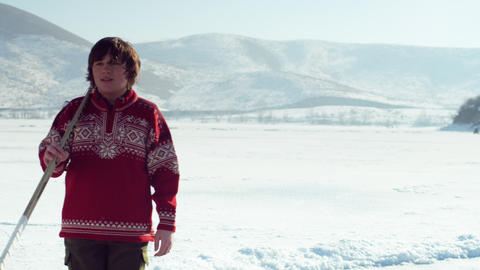 Young boy in a red sweater walking onto a frozen pond to play hockey Footage